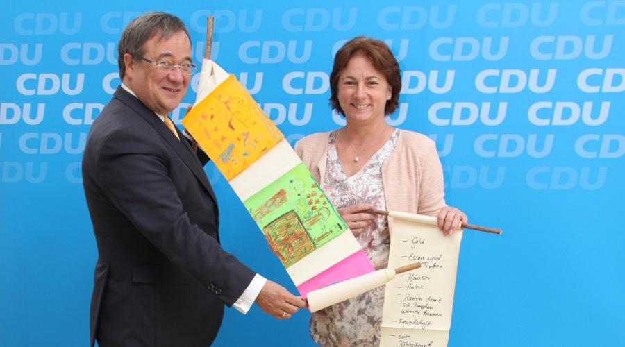 Ministerpräsident Armin Laschet übernimmt die Schriftrolle mit den Kinder-Wünschen aus dem Mühlenkreis von Bianca Winkelmann MdL